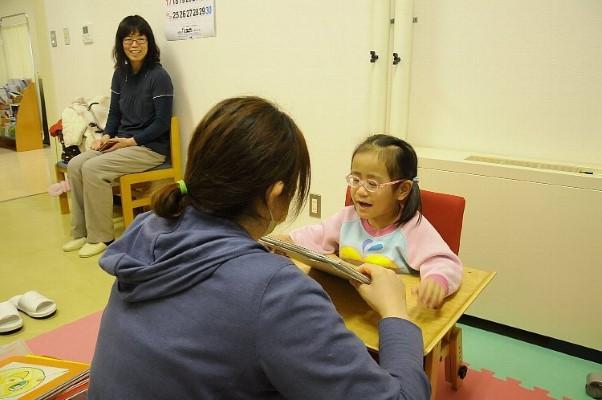 (作業療法士とリハビリに取り組む石田望笑ちゃん(右)。わが子の成長に由紀さん(左)がほほ笑む=1月下旬、青森市)